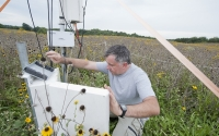 Researcher Terenzio Zenone checks carbon dioxide eddy flux instruments in a GLBRC / KBS LTER native prairie field; Photo Credit: K.Stepnitz, Michigan State University