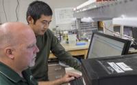Research associate Kevin Kahmark and graduate student Di Liang discuss peak integration on the laboratory GHG analysis system; Photo Credit: K. Stepnitz, Michigan State University
