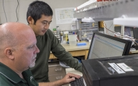 Research associate Kevin Kahmark and graduate student Di Liang discuss peak integration on the laboratory GHG analysis system; Photo Credit: K. Stepnitz, Michigan State University