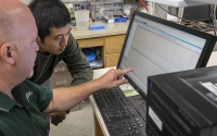 KBS LTER research technician Kevin Kahmark and graduate student Di Liang discuss chromatography results from the laboratory automated greenhouse gas analysis system; Photo Credit: K. Stepnitz, Michigan State University