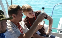 Journalists and scientists examine a water sample from Gull Lake during a Climate Change Communication workshop held at the KBS LTER in 2012; Photo Credit: B. Krasean, Michigan State University