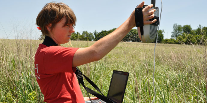 Undergraduate research intern takes canopy spectorgraph readings in a GLBRC / KBS LTER switchgrass biofuel field near KBS; Photo Credit: KBS LTER, Michigan State University