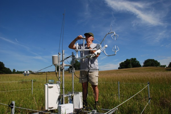 Scientist Terenzio Zenone checks the carbon dioxide instrument tower on a GLBRC / KBS LTER switchgrass field on the Marshall Farm. This equipment continuously monitors the carbon dioxide released or captured by the ecosystem, allowing scientists to quantify the impact of crop management on net carbon dioxide exchange over the long term, which in turn affects the climate. Photo Credit: B. Zenone