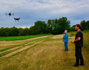 two researchers standing in ag field flying UAV